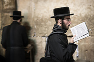 """A haredi man walking along the Kotel with a siddur, the daily prayer book. He has the characteristic haircut. Payot is the Hebrew word for sidelocks or sidecurls worn by some men and boys in the Orthodox Jewish community based on an interpretation of the Biblical injunction against shaving the """"corners"""" of one's head."""
