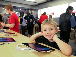 23 November 2012. New Orleans, Louisiana.<br /> Black Friday. A child plays with iPads at the Apple store as shoppers descend on discounted iPhones, iPads, computers and accessories on the traditional post Thanksgiving shopping frenzy.<br /> Photo; Charlie Varley/varleypix.com