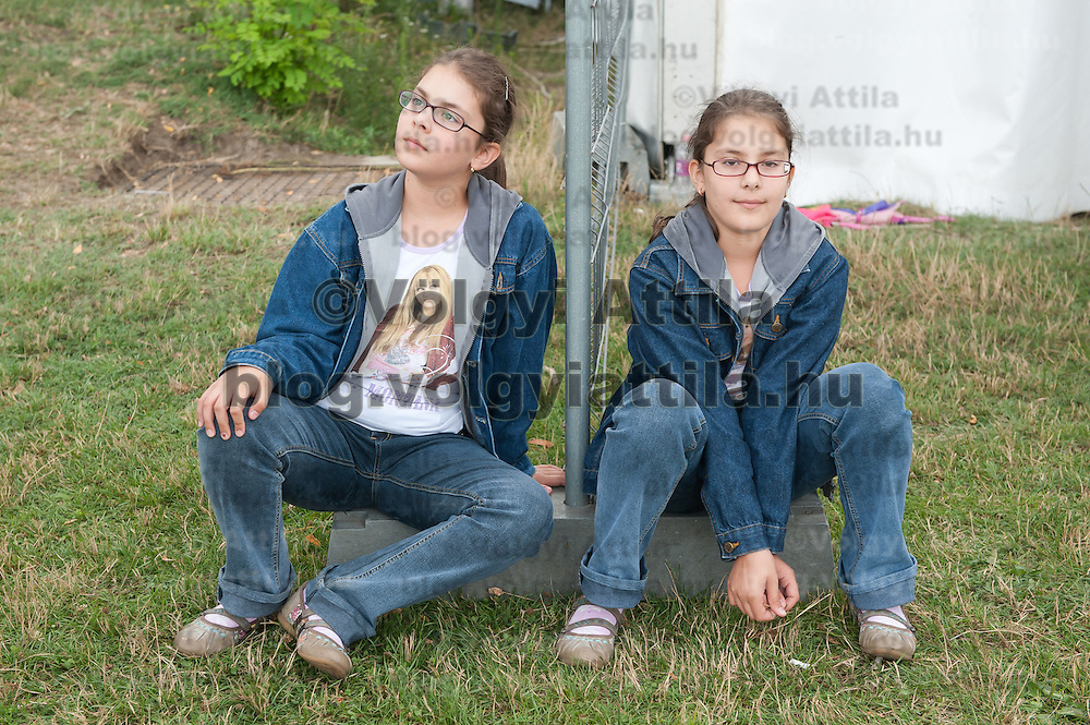 Two twins sit next to each other during the 12th Twin Festival held 7th time in Szigehalom (about 15 km from Budapest), Hungary on July 23, 2011. ATTILA VOLGYI