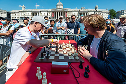 © Licensed to London News Pictures. 18/07/2021. LONDON, UK. Grandmaster Mickey Adams (L) takes on Peter Hornsby at Chess Fest in Trafalgar Square.  The event celebrates the game of chess and visitors can learn the game, play chess or challenge a Grandmaster.  Also, to celebrate the 150th anniversary of Lewis Carroll's Alice Through the Looking Glass book which featured the game of the chess, 32 actors dressed as Alice Through the Looking Glass characters stand on a giant chessboard replaying a game based on the book.  Photo credit: Stephen Chung/LNP