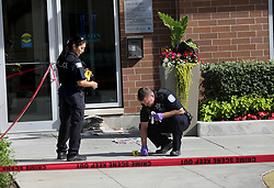 August 13, 2017 - Chicago, Il, USA - Police officers on the scene take a swab of blood from in front of the door to Wilson Yard.  A fatal shooting occurred in front of  the Wilson Yard Senior Living building at 1032 W. Montrose Avenue in Chicago Sunday Aug. 13, 2017 and police investigate the scene. (Credit Image: © Nancy Stone/TNS via ZUMA Wire)