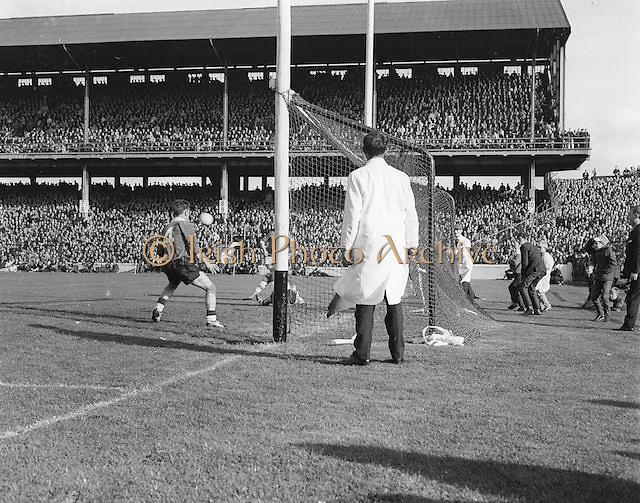 Umpire watches as Dublin makes a shot at the goal but it goes wide during the All Ireland Senior Gaelic Football final Dublin vs Derry in Croke Park on 28th September 1958. Dublin 2-12 Derry 1-9.