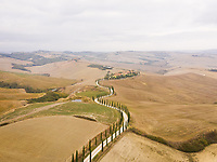 Aerial view of small road crossing mountain countryside landscape, Italy.