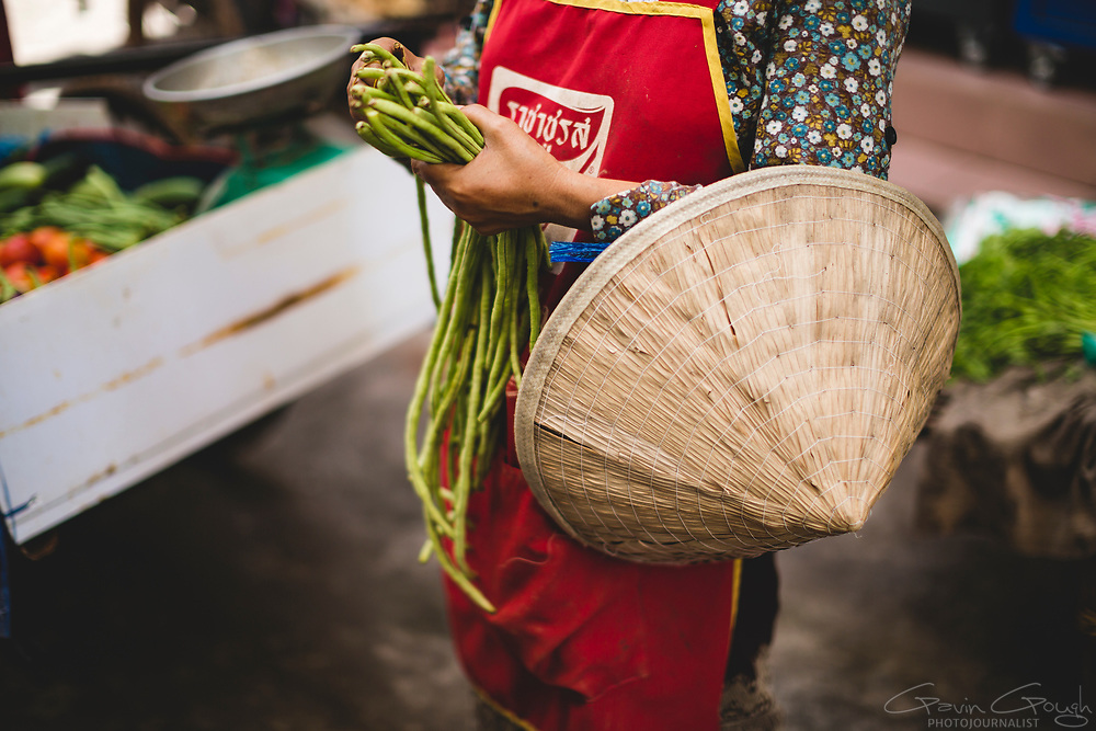 A street vendor carrying a traditional conical hat buying green beans from a street market, Vientiane City Centre, Vientiane, Laos