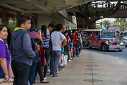 People queueing up to board the local free Jeepney in Makati, Metro Manila, Philippines. A Jeepneys, or 'Dyipni' in Filipino, are repurposed US military jeeps left over from WWII that have become a prevalent symbol of Philippine art and culture.
