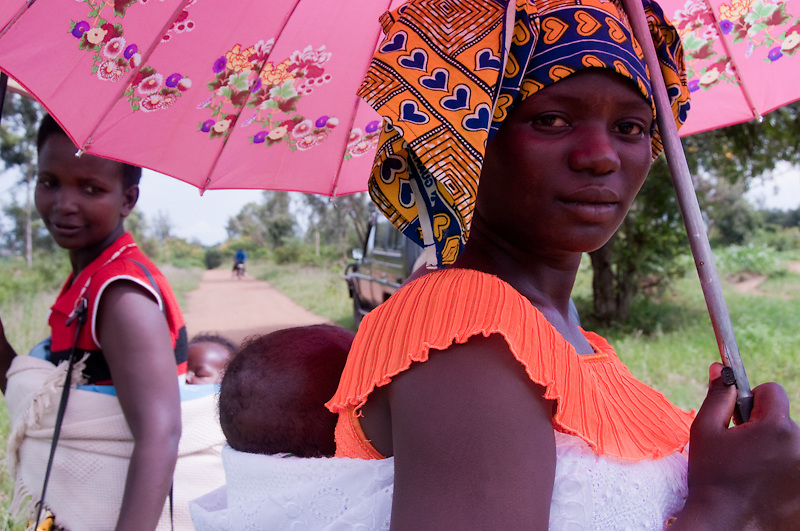 A young woman shades herself from the sun with a pink umbrella in Rwanda.