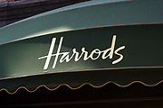 The world famous Harrods logo printed on a green awning over the Harrods department shop window, Knightsbridge, London, United Kingdom.