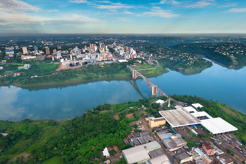 Aerial view of the Paraguayan city of Ciudad del Este and Friendship Bridge, connecting Paraguay and Brazil through the border over the Parana River, with Brazilian customs and immigrations facilities in the foreground.