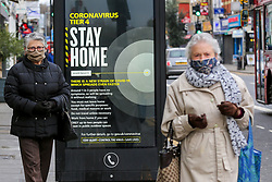 © Licensed to London News Pictures. 26/12/2020. London, UK. Elderly women wearing a face coverings in north London walk past the government's 'Coronavirus Tier 4 - Stay Home' publicity campaign poster as many parts of the UK entered the highest level of COVID-19 restrictions on Boxing Day after mutated COVID-19 strains continue to spread around the country. Prime Minister, Boris Johnson refused to rule out a third national lockdown in the New Year. Photo credit: Dinendra Haria/LNP