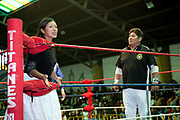 Female wrestler talking to crowd from in the ring, referee to the side. Lucha Libre wrestling origniated in Mexico, but is popular in other latin Amercian countries, including in La Paz / El Alto, Bolivia. Male and female fighters participate in the theatrical staged fights to an adoring crowd of locals and foreigners alike.