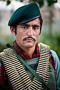 An Afghan National Army soldier wears belts of machine-gun ammunition wrapped around his torso.