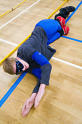 Team Player getting in position to block the ball from going into goal during a Goalball game; a threeaside game developed for the visually impaired and played on a volleyball court,