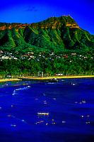 Surfers wait in water along Waikiki Beach with Diamond Head Crater in background, Honolulu, Hawaii USA