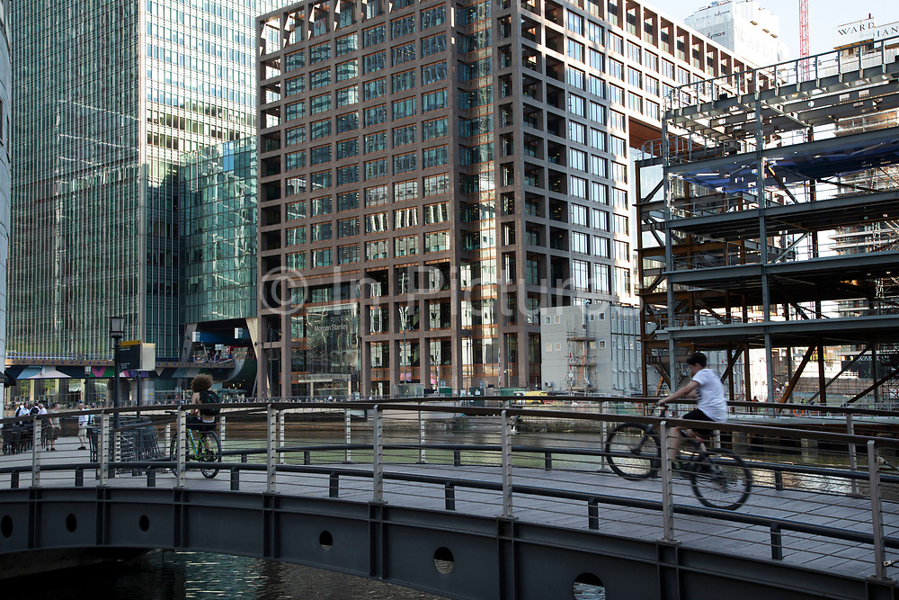 New construction opposite a footbridge across South Dock in Canary Wharf financial district in London, England, United Kingdom. Canary Wharf is a financial area which is still growing as construction of new skyscrapers continues.