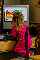 Little girl playing on the computer in her family's kitchen, Littleton, Colorado USA.