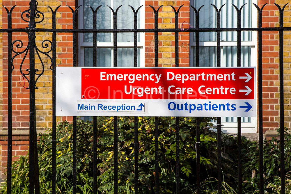Public sign on metal fence directing people to the Emergency Department, Urgent Care Centre, Outpatients and Main Reception of University Hospital Lewisham NHS Trust, South London, UK.