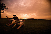 Adirondack chairs sit on a grassy field at sunset.