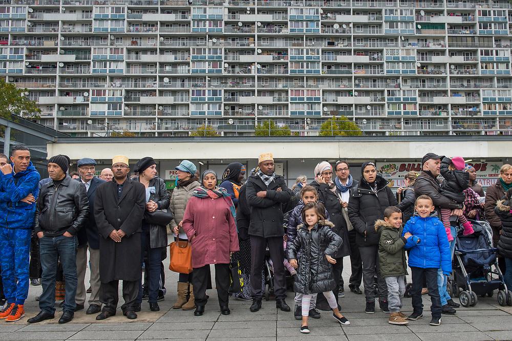 """20 octobre 2015, La Courneuve, France.<br /> Les résidents de La Courneuve, une banlieue à 5 km de Paris, attendent la visite du président François Hollande. En arrière-plan, les 15 étages de haut appartement courrier complexe de Fontenay, une partie des soi-disant «4000» complexes, des appartements qui ont été construits ici en 1964,<br /> <br /> October 20, 2015, La Courneuve, France.<br /> Residents from La Courneuve, a suburb at 5 km from Paris, wait for the visit of President Francois Hollande. In the background, the 15-story high apartment complex Mail de Fontenay, part of the so called """"4000"""" complex, flats that have been built here in 1964,"""