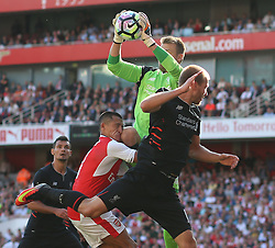 14 August 2016 London - Premier League Football : Arsenal v Liverpool :<br /> Alexis Sanchez of Arsenal gets the knee of Simon Mignolet in his face.<br /> Photo: Mark Leech