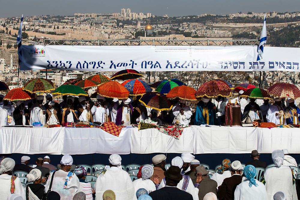 """Ethiopian Jewish community leaders or 'Kessim' hold umbrellas as they pray during a ceremony marking the 'Sigd' Ethiopian Jewish holiday at a hilltop in Jerusalem, Israel, on November 20, 2014. The holiday symbolizes the community's desire and aspirations for """"return to Jerusalem"""". It is celebrated in the holy city with thousands of Ethiopians from all over Israel congregating to pray together at a promenade overlooking the golden Dome of the Rock Islamic shrine and Jerusalem's Old City."""