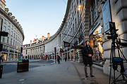 A man crosses an eerily quiet Regent Street in the early evening at Oxford Circus in London on March 27th, 2020. The centre of London is extremely quiet with almost every business closed and very few people about because of the Governments lockdown measures due to the Coronavirus crisis.