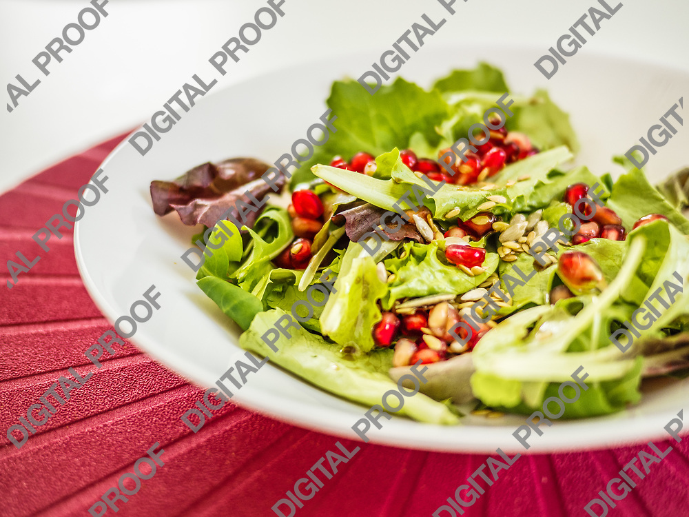 Healthy salad of fresh vegetables and pomegranate seeds on white dish