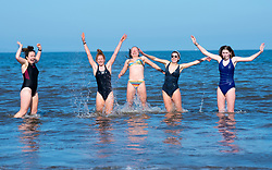 Portobello, Scotland, UK. 3 April 2021. Easter weekend crowds descend on Portobello beach and promenade to make the most of newly relaxed  Covid-19 lockdown travel restrictions and warm sunshine with uninterrupted blue skies. Pic;  Five young women from Edinburgh enjoy a dip in the sea. Iain Masterton/Alamy Live News