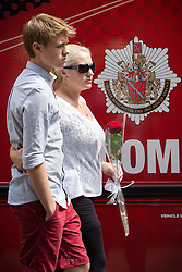 © Licensed to London News Pictures . FILE PICTURE DATED 15/07/2013 . Oldham Street , Manchester , UK . Stephen Hunt's family arrive at the scene . Son Sam (maroon shorts , 15) and ex-wife  Zoe (white top, black pants, sunglasses) . The scene on Oldham Street following a fire at Paul 's Hair World on 13th July which claimed the life of fireman Stephen Hunt . Photo credit : Joel Goodman/LNP