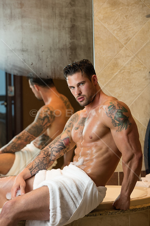 hot man with tattoos in a towel after a bath