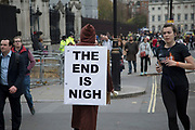 Demonstrator with a sandwich board reading The End Is Nigh protests in Westminster on Budget Day on 22nd November 2017 in London, England, United Kingdom. As the Tories deliver their Autumn Budget, protesters make their views heard outside Parliament.