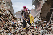 A woman wearing a scarf for protection from the dust salvages belongings from a family home that was destroyed during the 2015 Nepal earthquake.