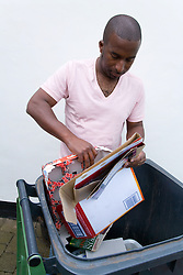 Man putting cardboard in recycling wheelie bin ready for collection,