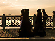 08 AUGUST 2007 -- ISTANBUL, TURKEY: Turkish women in traditional Moslem dress cross the Galata Bridge across the Golden Horn in Istanbul, Turkey. Istanbul, a city of about 14 million people, and the largest city in Turkey, straddles the Bosphorus Straits between Europe and Asia. It is one of the oldest cities in the world. It was once the center of the Eastern Roman Empire and was called Constantinople, named after the Roman Emperor Constantine. In 1453, Mehmet the Conqueror, Sultan of the Ottoman Empire, captured the city and made it the center of the Ottoman Turkish Empire until World War I. After the war, the Ottoman Empire was dissolved and modern Turkey created. The capitol was moved to Ankara but Istanbul (formerly Constantinople) has remained the largest, most diverse city in Turkey.    Photo by Jack Kurtz
