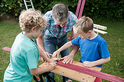 Father sons working garden building wood