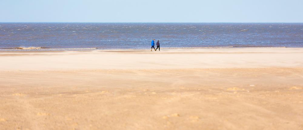 People walking along Holkham Beach, a vast sandy beach on North Norfolk coast, UK
