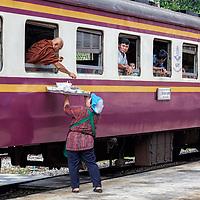 A woman selling food to a monk at Hua Hin train station.