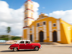 North America, Caribbean, Cuba, Remedios, classic red car in front of Cathedral