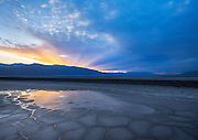 Sunset over the Panamint Mountains and a pond on the Badwater Salt Flat in Death Valley National Park, California