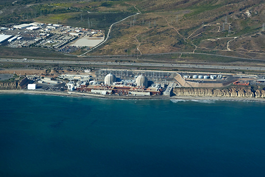 View of the San Onofre Nuclear Generating Station from the air looking north/northeast. The 84-acre (34 ha) site is in the northwestern corner of San Diego County, south of San Clemente, and surrounded by the San Onofre State Park. It provides nearly 20% of the electrical power to the residents of Southern California (wiki 2009).