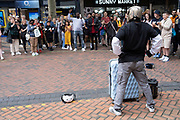 Crowd of onlookers gathers to watch a break dancing and body popping street performer on New Street in the city centre on 3rd August 2021 in Birmingham, United Kingdom. Wearing a helmet as if a robot this street dancer is busking for monetary donations.