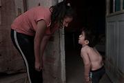 """Alayn (3) y su mamá Yamila (19) en la puerta de la habitación que alquilan para vivir. Alayn nació con la patología mucopolisacaridosis tipo IV. Esta refiere a la falta de enzimas para descomponer cadenas largas de moléculas de azúcar. Las mismas se acumulan en distintas partes del cuerpo originando problemas de salud en todos los órganos, huesos y sistemas. Yamila no tuvo ningún diagnóstico prenatal sobre la condición de Alayn siendo que su detección temprana hubiese podido ayudar a retrasar algunas de las graves consecuencias de esta patología. Por el contrario, pasaron varios meses desde el nacimiento del niño hasta que tuvo el diagnóstico. """"Yo soy la única que cuida de él. Es difícil tratar de buscar soluciones. Los médicos te indican una cosa y la obra social no lo cubre. Yo estoy sola para todo, el papá se fue cuando estaba embarazada."""" -Dice Yamila- El tratamiento de reemplazo enzimático de Alayn es uno de los más costosos del mundo, razón por la cual, siempre se interponen obstáculos económicos de las obras sociales para garantizar el derecho a la salud. El aislamiento geográfico, la desidia Estatal, la ausencia de controles y regulaciones sanitarias inciden drásticamente en la posibilidad de que estos niños reciban sus tratamientos en tiempo y forma adecuados. Cuestión que se profundizó gravemente a causa de la emergencia pública en materia sanitaria debido a la pandemia por Covid-19. Durante el año 2020 el tratamiento para Alayn se ha visto suspendido y postergado"""
