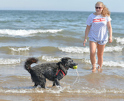 3 year old Romanian rescue dog Lilly cools down in the surf with her owner Alice Grove (14) from Newtingrange at Portobello beach, on what is predicted to be the hottest day of the year.<br /> <br /> © Dave Johnston / EEm