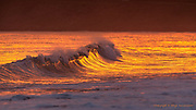Embers of an evening fire in the sky, illuminated gentle sets of peeling waves rolling towards the beach at Hell's Mouth in North Wales.