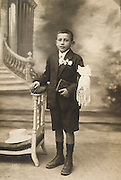 young boy posing to commemorate his first holy communion 1920s