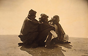 Three Navajo men, seated on ground, turned right, c1904.  Photograph by Edward Curtis (1868-1952).