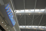 Looking upwards to WH Smiths retail sign in landside Departures area newly-opened London Heathrow Airport's Terminal 5 building