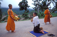 Luang Prabang, Laos, a UNESCO World Heritage Center..woman giving offering of rice and fish to monks..