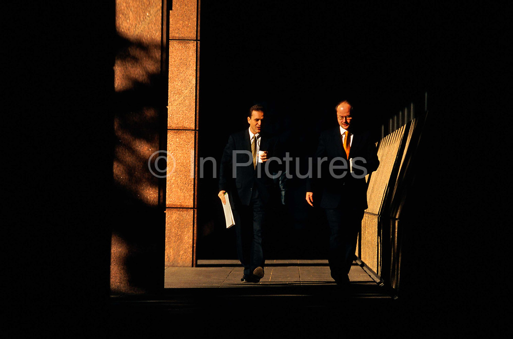 Two businessmen - one younger than the other, who may be his superior - pace through the Broadgate Estate during a break in the working day in the City of London, the capital's financial centre - otherwise called the Square Mile. Seen as they walk fast under a covered alleyway, the warm sun strikes their faces while they are deep in conversation - perhaps discussing a strategy while fetching a local coffee. Deep shadow allows us to focus in on their dark suits, their pink skin and the similarly orange colour of the strong vertical columns that form this urban architecture completed in the Bishopsgate development of the mid-1980s. Broadgate is a large, 32 acres (129,499 m2) office and retail estate in the City of London, owned by British Land and managed by Broadgate Estates.