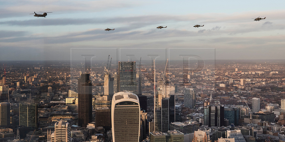 NOTE TO EDITORS - SHOT THROUGH A WINDOW, SOME REFLECTIONS ARE VISIBLE (L)  © Licensed to London News Pictures. 16/01/2018. London, UK.  The last four remaining British Army Lynx helicopters are escorted by a Chinook as they fly in formation over The City of London. The British made aircraft is being decommissioned after almost 40 years in service. Photo credit: Peter Macdiarmid/LNP