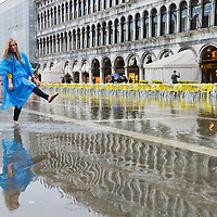 VENICE, ITALY - JUNE 07:   Tourists in St Mark's Square seems to enjoy the unusual high water that has flooded the square this afernooni on June 7, 2011 in Venice, Italy. Thunderstorms and heavy rain have hit Venice causing an out season high tide of 90 cm flooding St Mark's square.  San Marco is one of the six sestieri of Venice, lying in the heart of the city.